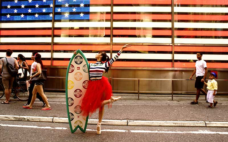 photo: Georgina Pazcoguin with surfboard and American flag